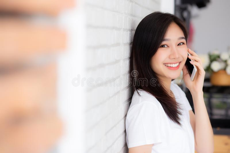 Beautiful of portrait young asian woman talk smart phone and smile standing on cement brick background, freelance female calling royalty free stock photography