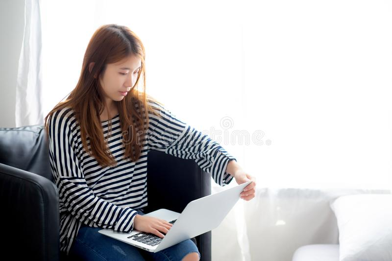 Beautiful of portrait young asian woman using laptop computer for leisure on chair at living room, girl working online with royalty free stock images