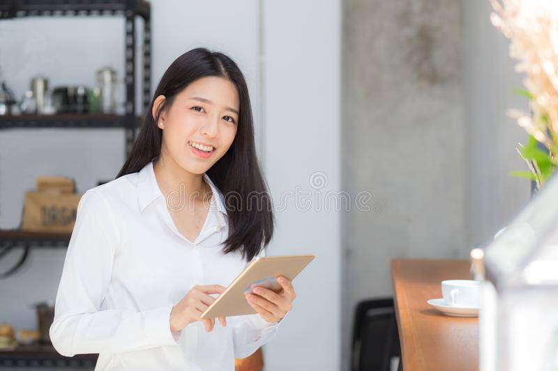 Beautiful portrait young asian woman using tablet computer in the coffee shop. stock image