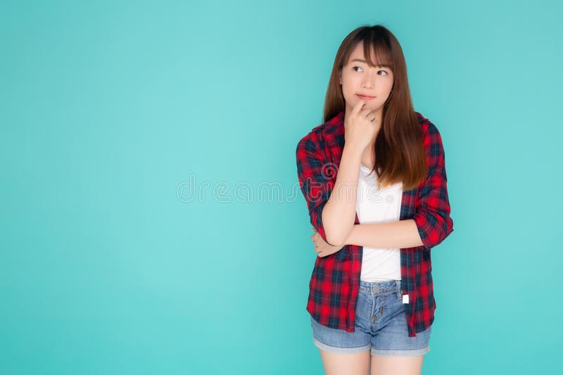 Beautiful portrait young asian woman wear clothes fashion travel thinking idea and enjoy summer holiday. Blue background, girl smiling confident and cheerful stock photography