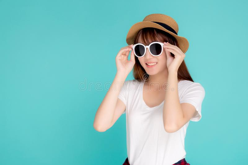Beautiful portrait young asian woman wear hat and holding sunglasses smiling confident enjoy journey summer trip in vacation stock photo