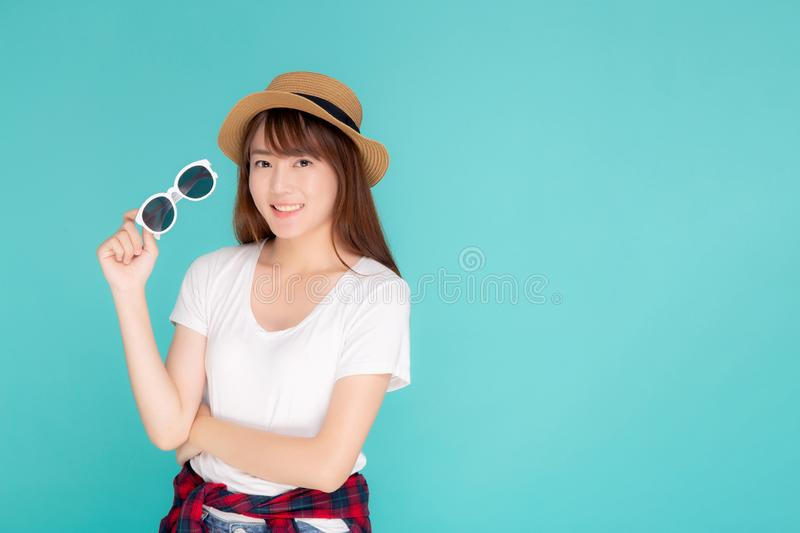 Beautiful portrait young asian woman wear hat and holding sunglasses smiling expression confident enjoy summer in vacation royalty free stock photography
