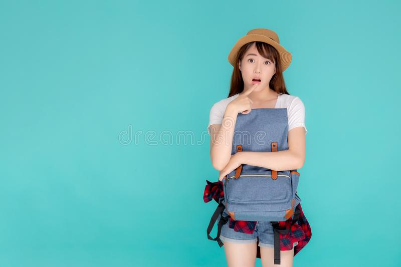 Beautiful portrait young asian woman wearing hat smiling and thinking idea with holding backpack to travel summer trip. In holiday in vacation isolated blue royalty free stock image