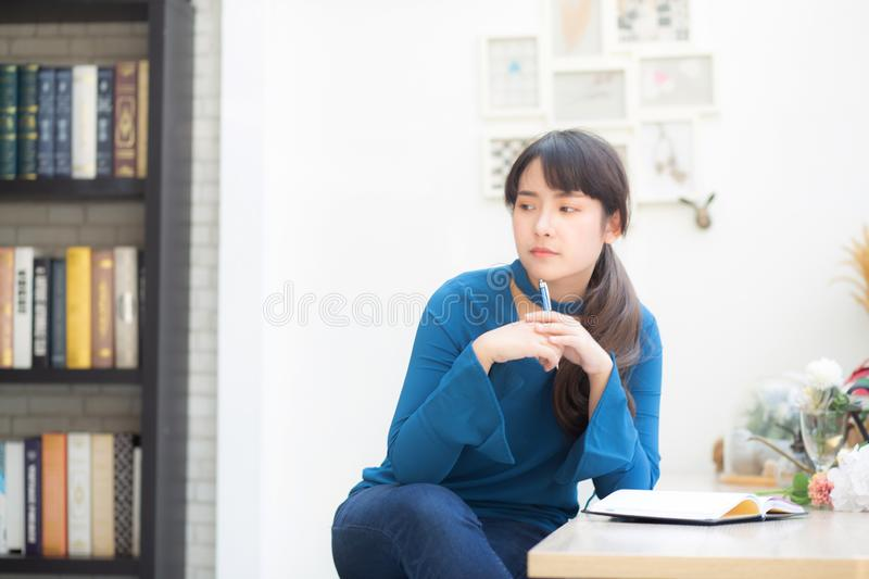Beautiful portrait young asian woman writer smiling thinking idea and writing on notebook or diary with happy. Lifestyle of asian girl is student, female royalty free stock photo