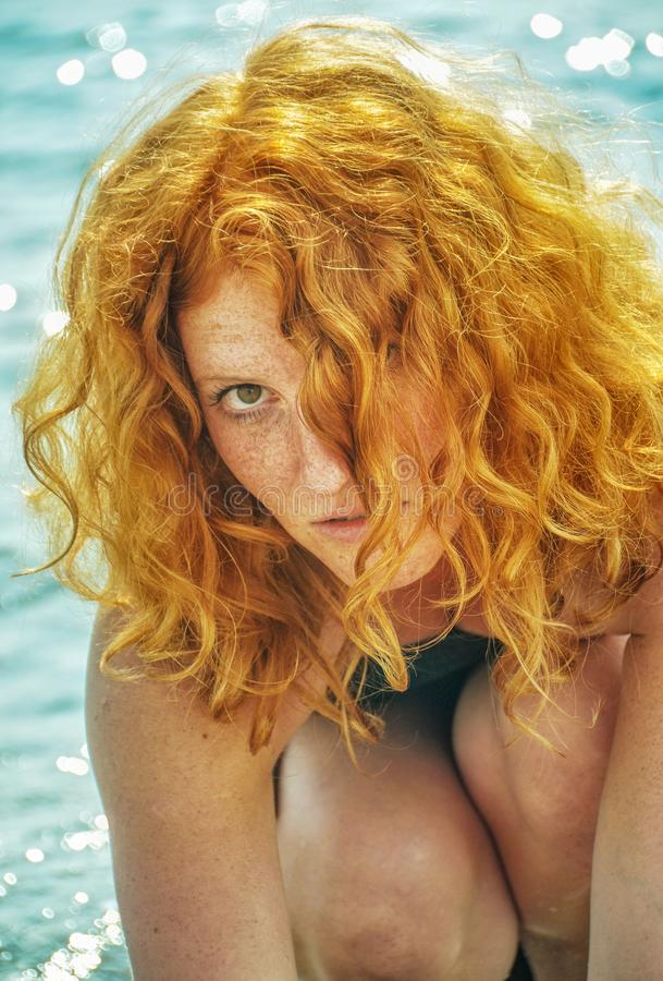 Beautiful portrait of a young elegant sexy red-haired curly woman sitting at the beach royalty free stock images