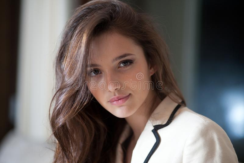 Close up portrait of a beautiful young business woman with long brunette hair posing in stylish suit, looking at camera. royalty free stock images