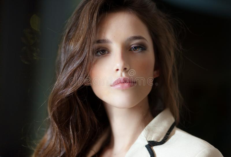 Frontal portrait of a young woman with long hair, wearing in delicate suit, looking at camera, blurry room background. Beautiful portrait of a young elegant stock image