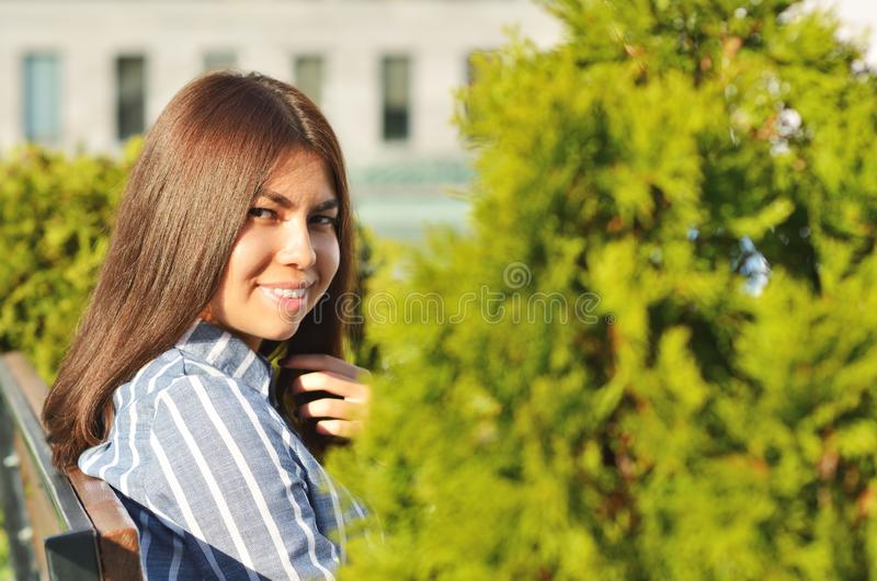 Beautiful portrait of a young girl who talks on the phone in the city Park. Near the beautiful green spaces royalty free stock images