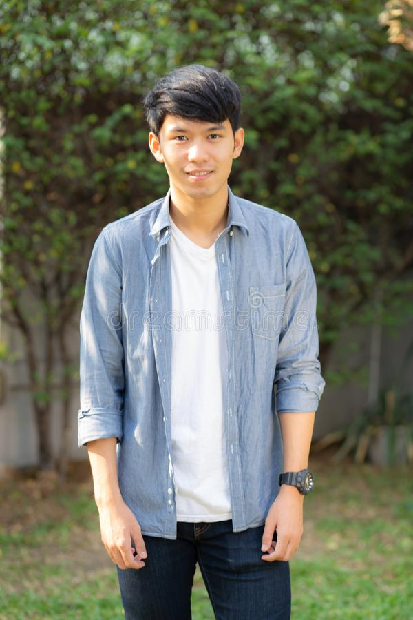Beautiful portrait young handsome asian man standing and smile with sunlight at morning royalty free stock images