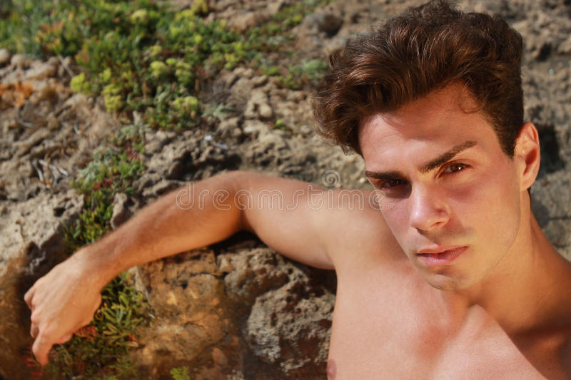 Beautiful portrait young man shirtless outdoor on the rocks. A beautiful young Italian man posing at the sea shirtless on the rocks / serious and sure of himself royalty free stock photography