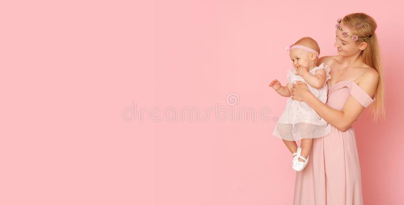 Beautiful portrait of young mom and her little, cute daughter. The picture full of love. Beautiful mum and her little daughter in ceremonial pink dresses royalty free stock photo