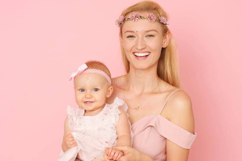 Beautiful portrait of young mom and her little, cute daughter. The picture full of love. Beautiful mum and her little daughter in ceremonial pink dresses stock image