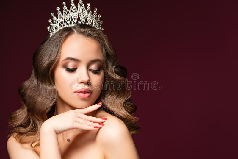 Beautiful portrait of young woman with perfect make-up, hairstyle, and nail design. Beauty contest. Crown on her head stock photography