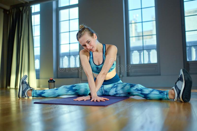 Beautiful portrait of young woman relaxing form exercise and smiling during a break in the gym. Caucasian female sitting royalty free stock images