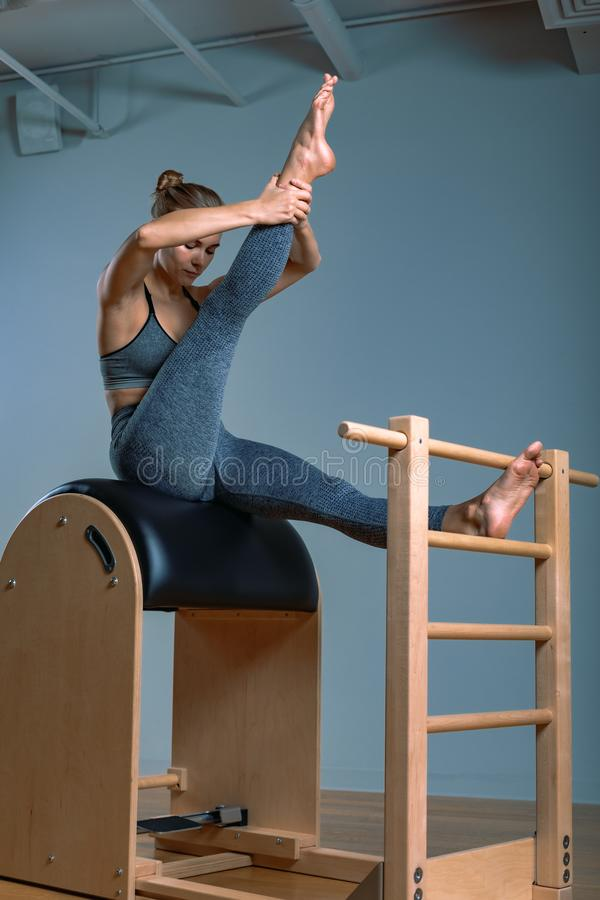 Beautiful positive blond woman is being prepared performing pilates exercise, training on barrel equipment. Fitness stock image