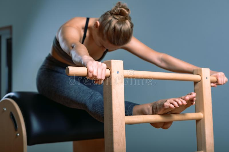 Beautiful positive blond woman is being prepared performing pilates exercise, training on barrel equipment. Fitness stock photos
