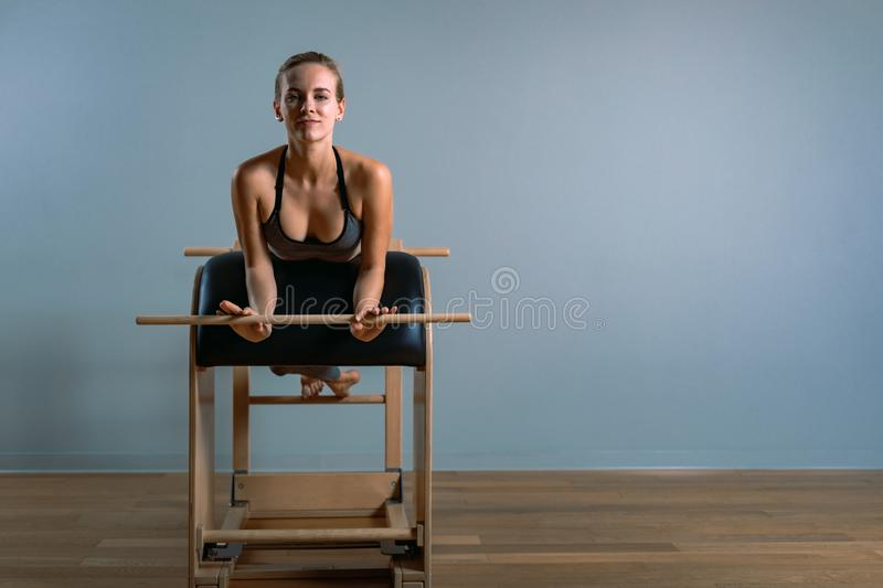 Beautiful positive blond woman is being prepared performing pilates exercise, training on barrel equipment. Fitness stock photo
