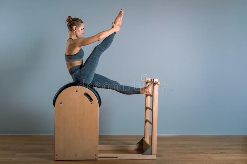Beautiful positive blond woman is being prepared performing pilates exercise, training on barrel equipment. Fitness royalty free stock images