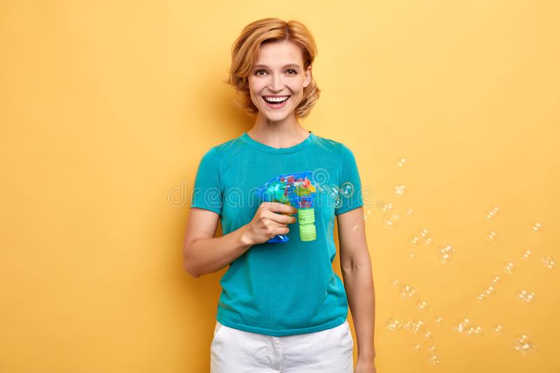 Beautiful positive girl in blue T-shirt making soap bubbles stock photo