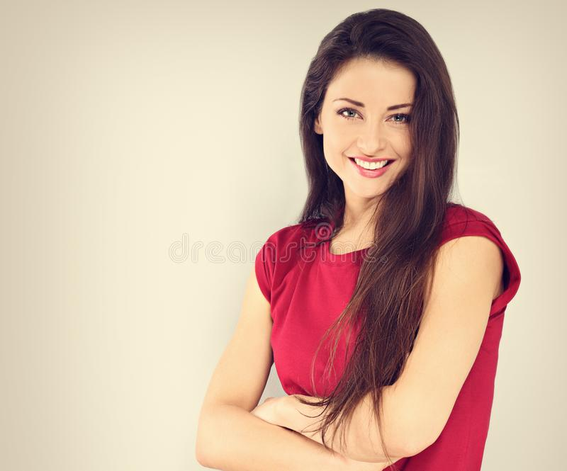 Beautiful positive toothy smiling woman with folded arms looking happy in casual red shirt on vintage toned background. With empty copy space royalty free stock photography