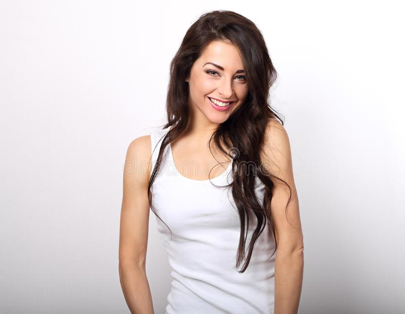 Beautiful positive woman in white shirt and long hair toothy smile on white background royalty free stock images