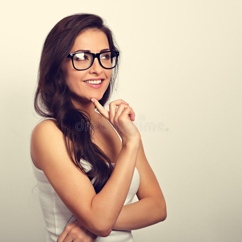 Beautiful positive young casual woman with folded arms in glasses thinking and looking up in white shirt and long hair. Toned royalty free stock image