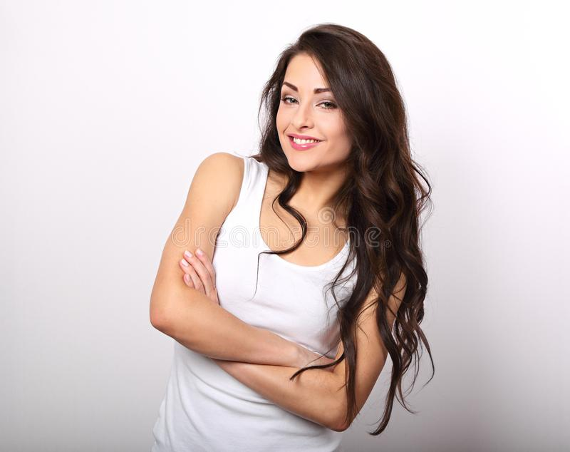 Beautiful positive young casual woman with folded arms in white royalty free stock photo
