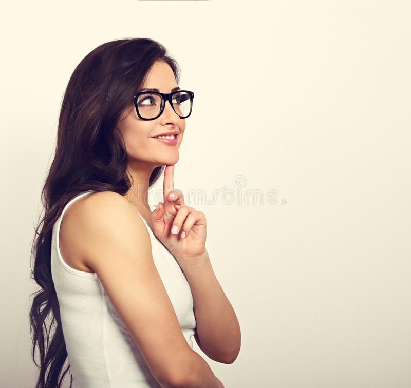 Beautiful positive young casual woman profile view with folded a. Rms in glasses thinking and looking up in white shirt and long hair. Toned vintage portrait royalty free stock photos