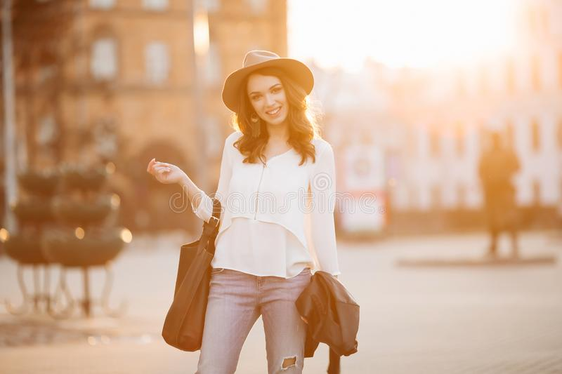 Brunette woman in hat walking at sunset after shopping. royalty free stock images