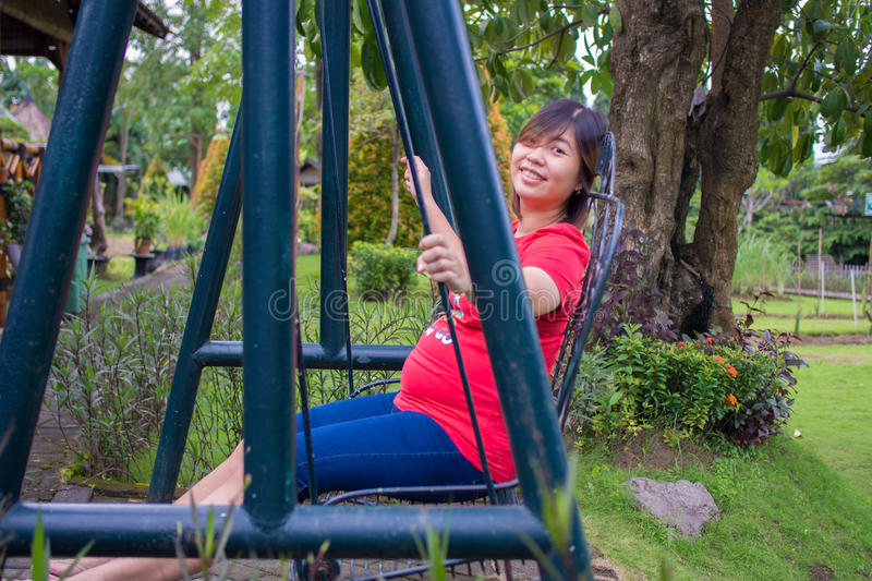 Beautiful Pregnant Asian - Chinese Woman Smiling Playing Swing o stock images