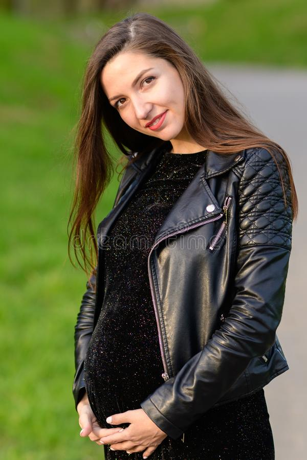 Beautiful pregnant brunette. Beautiful pregnant woman. Gorgeous pregnant girl outdoors. Brunette with long hair lady - happy stock photo