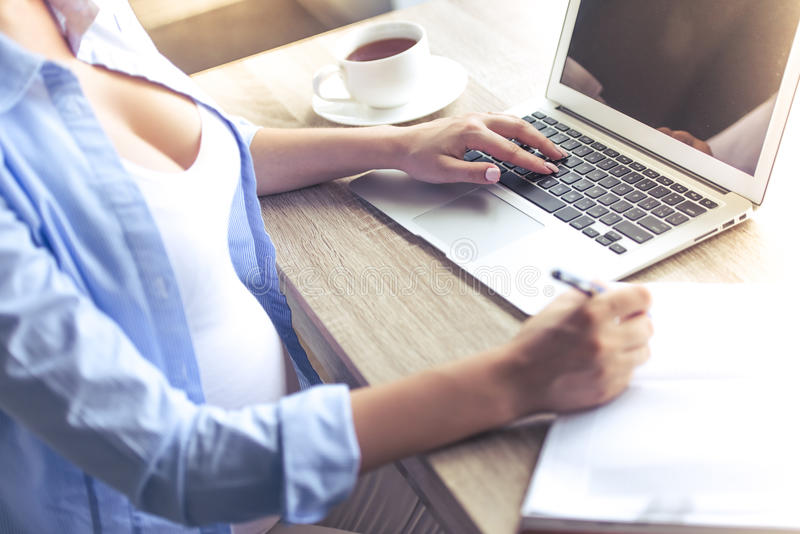 Beautiful pregnant business woman. Cropped image of beautiful pregnant business woman using a laptop and making notes while working at home royalty free stock photo