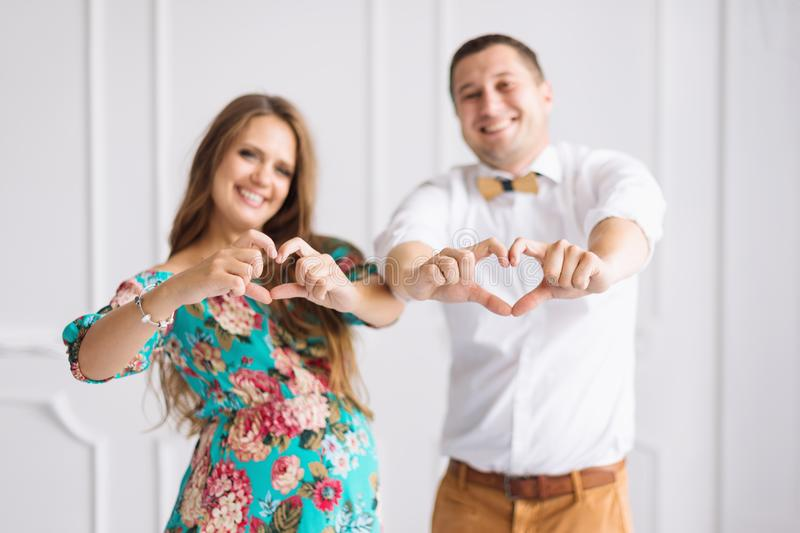 Beautiful pregnant couple happy together expecting a child. Man and woman in white minimalistic interior showing hearts with hands. Beautiful pregnant couple royalty free stock photos