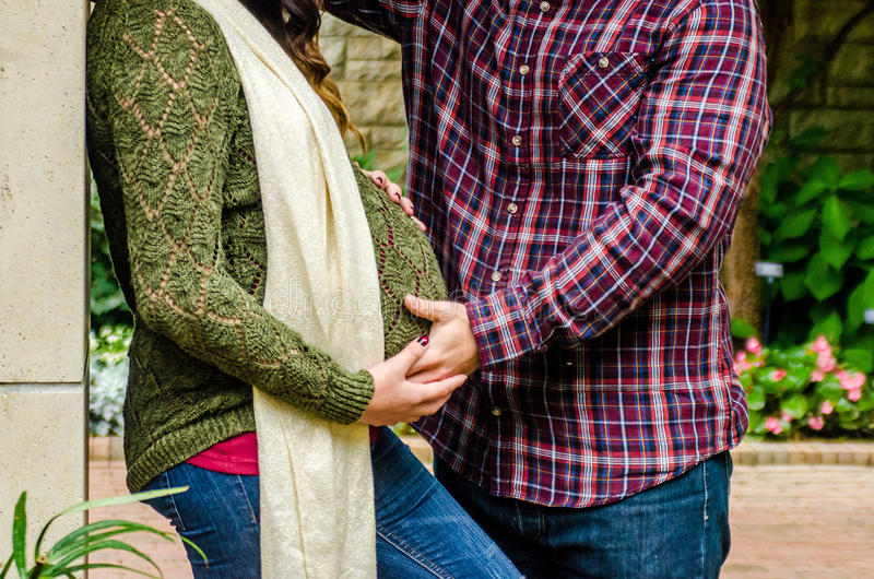 Beautiful pregnant couple. / lady / girl / young women in her last trimester showing her stomach / belly with her spouse / husband / men / guy in Fall clothing royalty free stock photo