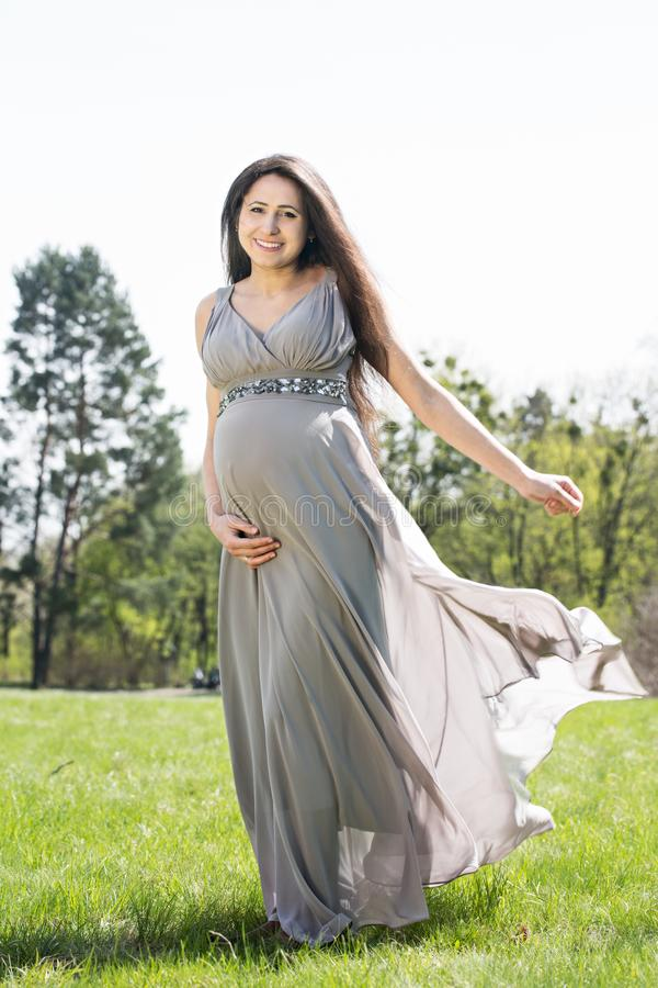 Pregnant woman on a spring meadow royalty free stock images