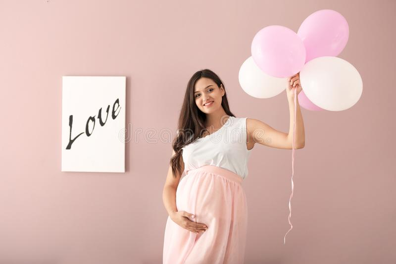 Beautiful pregnant woman with air balloons on color background royalty free stock photos