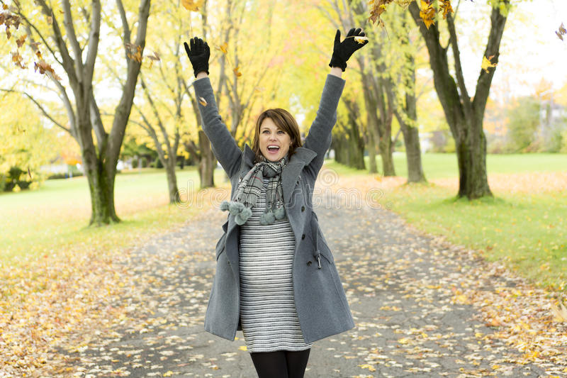 Beautiful pregnant woman in the autumn park stock photo