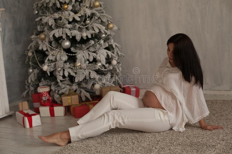 Beautiful pregnant woman at the Christmas tree with gifts for the new year. Beautiful pregnant woman at the Christmas tree with gifts stock photos