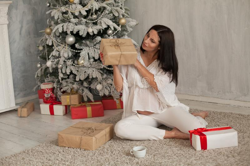 Beautiful pregnant woman at the Christmas tree with gifts for the new year. Beautiful pregnant woman at the Christmas tree with gifts stock photography
