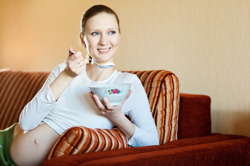 Beautiful pregnant woman eating cottage cheese royalty free stock photo