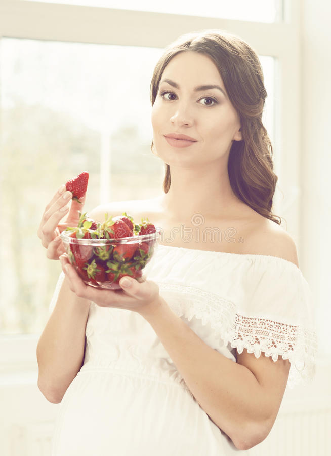 Beautiful pregnant woman eating strawberries in kitchen. Motherhood, pregnancy, maternity concept. royalty free stock images
