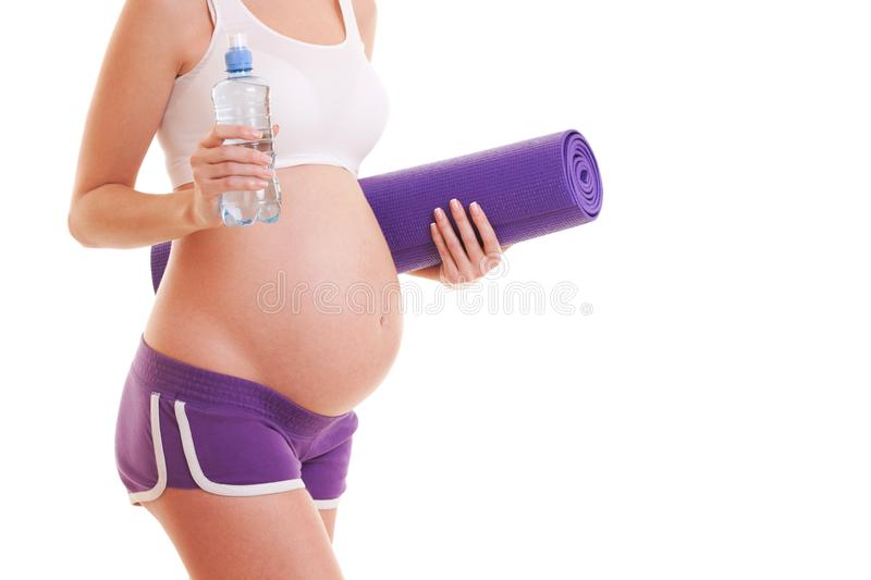 Beautiful pregnant woman with exercising mat and water on white background. Healthy lifestyle. Motherhood, pregnancy, people and stock photography