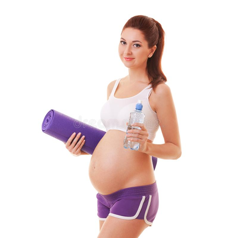 Beautiful pregnant woman with exercising mat and water on white background. Healthy lifestyle. Motherhood, pregnancy, people stock photography