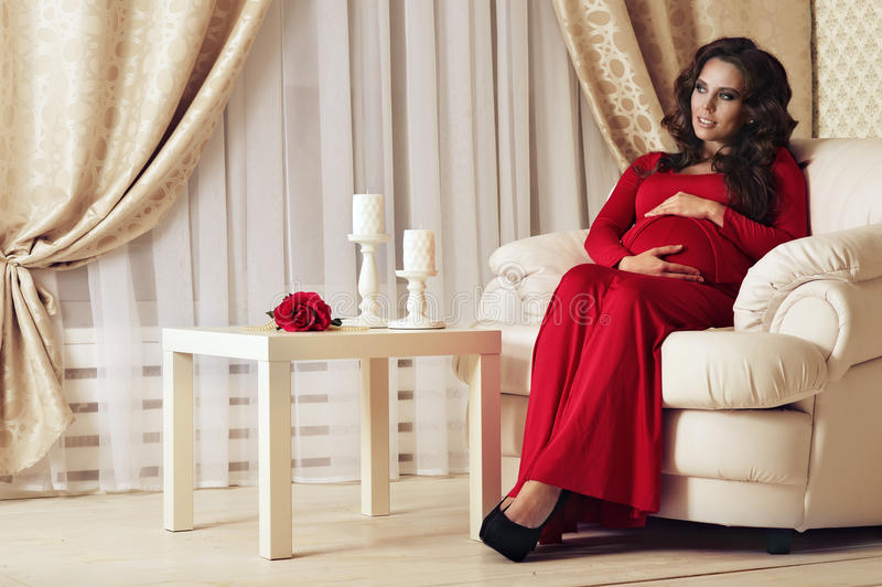 Beautiful pregnant woman. Fashion photo of beautiful pregnant woman with long dark hair posing in beautiful interior royalty free stock photo