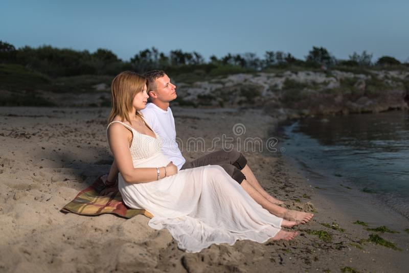 Beautiful pregnant woman and her man  sitting on the seashore stock image