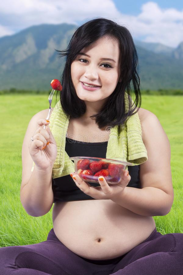 Beautiful pregnant woman holding a bowl of strawberry at meadow stock photo