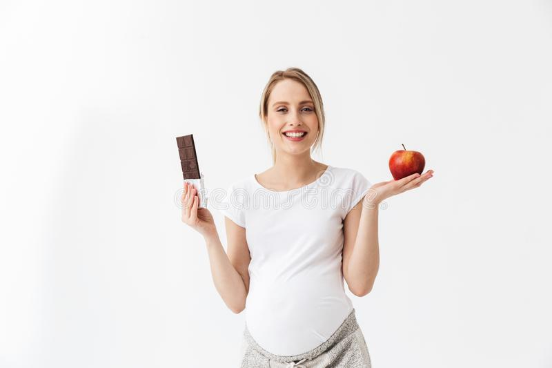 Beautiful pregnant woman holding chocolate bar and red apple stock image