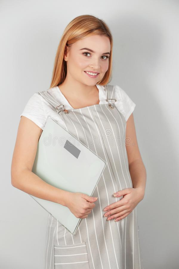 Beautiful pregnant woman holding scales royalty free stock photo