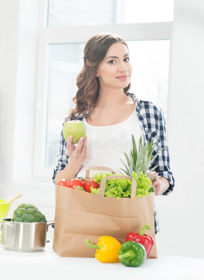 Beautiful pregnant woman in the kitchen with shopping bag and apple royalty free stock photography