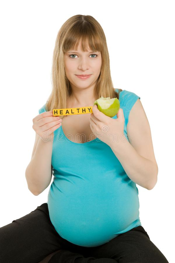 Beautiful pregnant woman looking to the camera and holding an ap stock photo